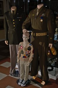 Six year old Bobbie Hinshaw wearing the original WW II sweater on which his grandmother sewed patches given to him by soldiers and Marines on the troop trains from California to Kansas in 1942. He is with Capt. Everett King of the 44th Infantry Division and Sgt Arthur Mills of the 464th Bomb Group who was a POW in Germany.