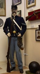 Civil War Corporal with the 9th Maine Volunteer Infantry Regiment. One of only two reproduction uniforms in the museum. The re-enactors uniform is accurate down to the buttons. The weapons are authentic.