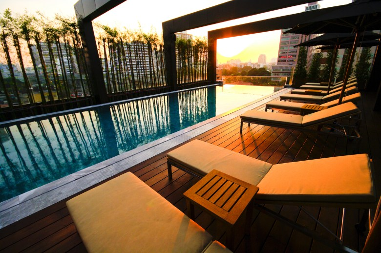 Pool with chair on rooftop hotel