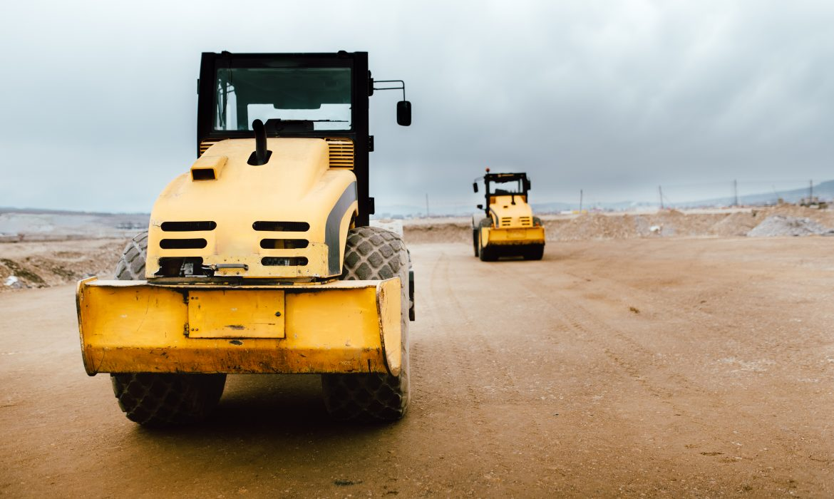 Two Vibratory Soil Compactors on construction site. Industrial roadworks at highway with heavy-duty machinery