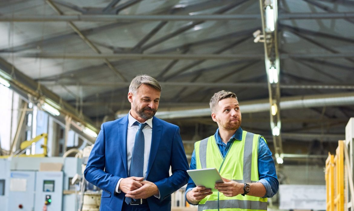 Waist up portrait of young workman giving tour of modern factory to handsome mature businessman, copy space