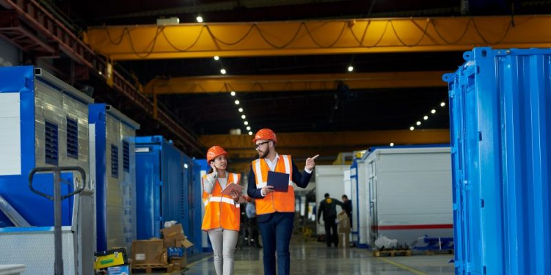 Full length  portrait of bearded businessman wearing hardhat talking to female factory worker while discussing production in workshop, copy space