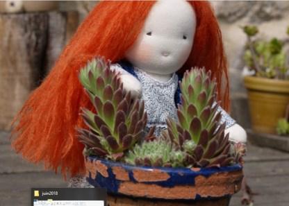 Photo de la poupée rousse derrière des plantes grasses