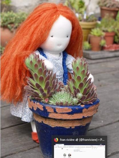 Photo de la poupée rousse derrière des plantes grasses plan 3 légèrement plus large