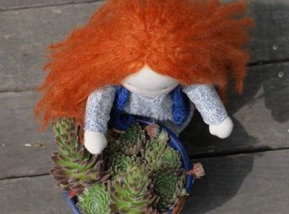 Photo en plongé de la poupée rousse derrière des plantes grasses