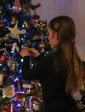 Katie decorating the tree with handmade ornaments for sale.