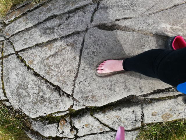A close up of my bare foot in the carved rock footprint on Dunadd.