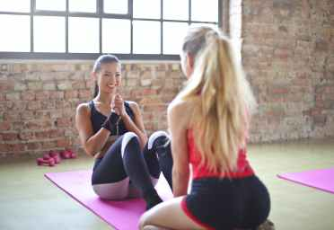 woman with red top and black shorts on purple yoga mat