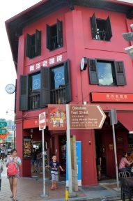 Placas escritas em chinês, edifício vermelho em Singapura