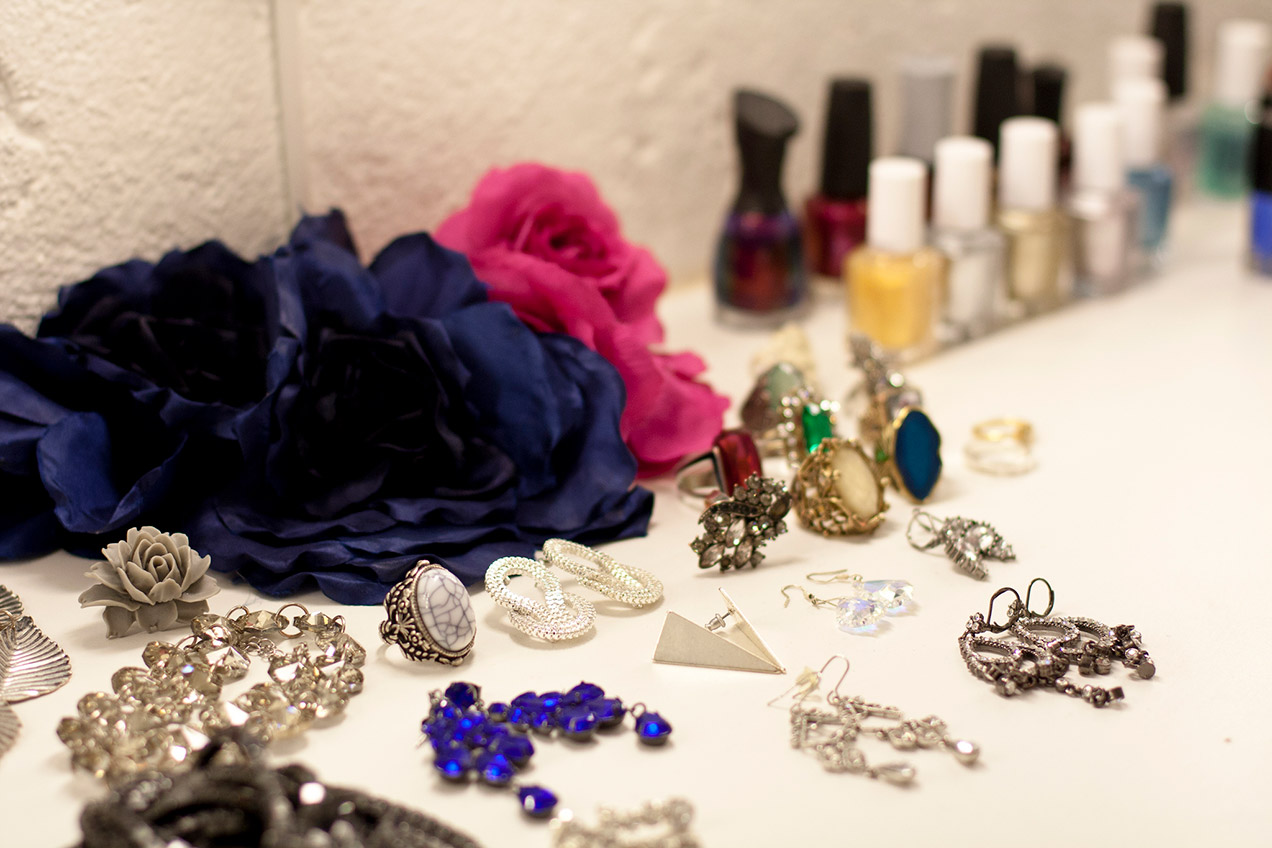 Accessories and nail polish neatly placed on a white tabletop