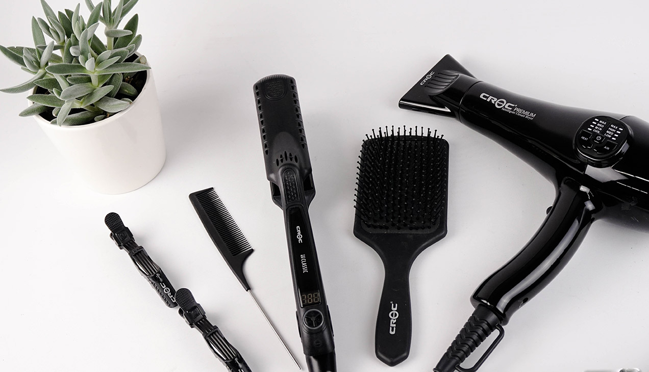 Black hair care tools on a white table