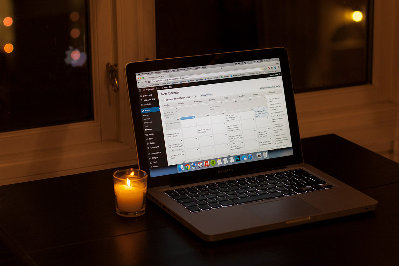 Laptop with a small candle next to it. On the screen there is a Wordpress editorial calendar.