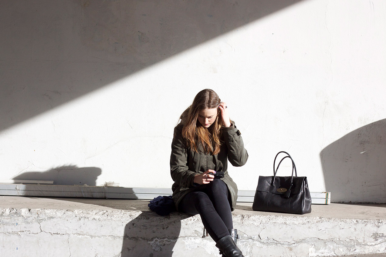 Girl sitting on ledge with a black Mulberry Bayswater handbag next to her