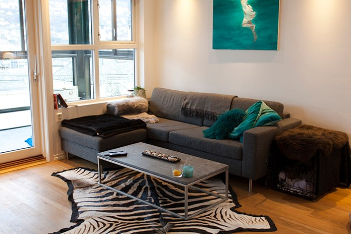 Bright living room featuring a gray couch, a gray marble coffee table, and a zebra skin rug