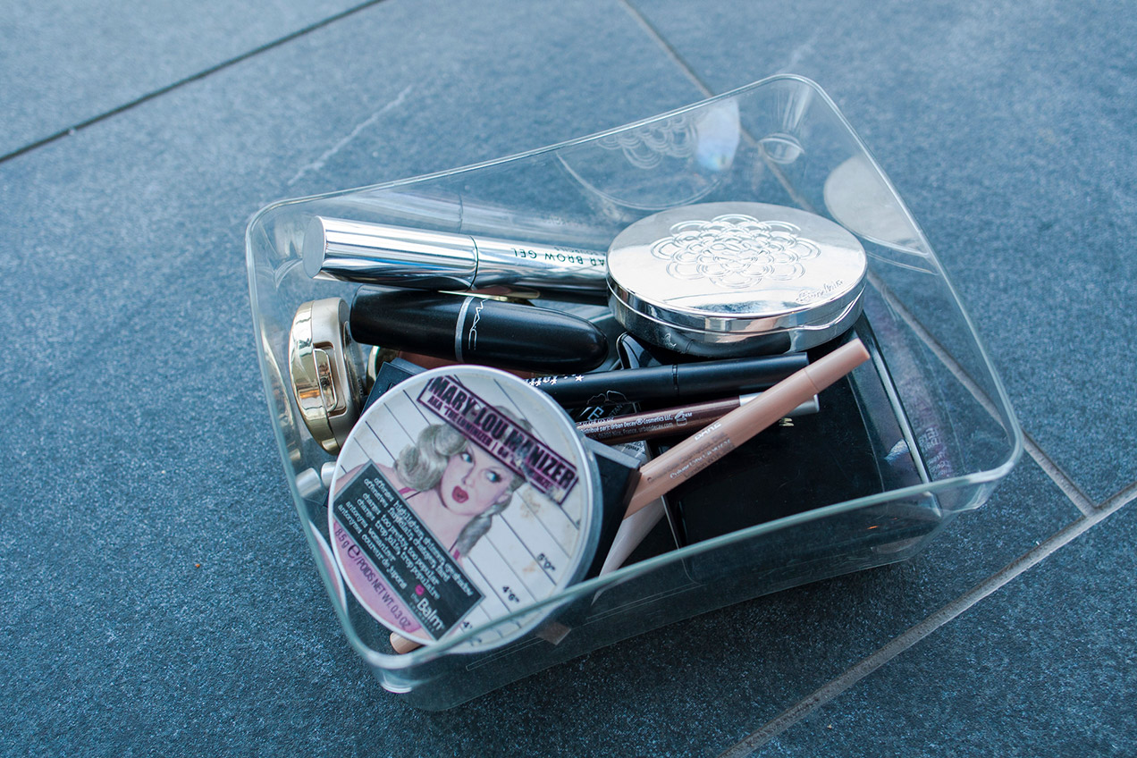 Clear plastic box with a small collection of makeup inside