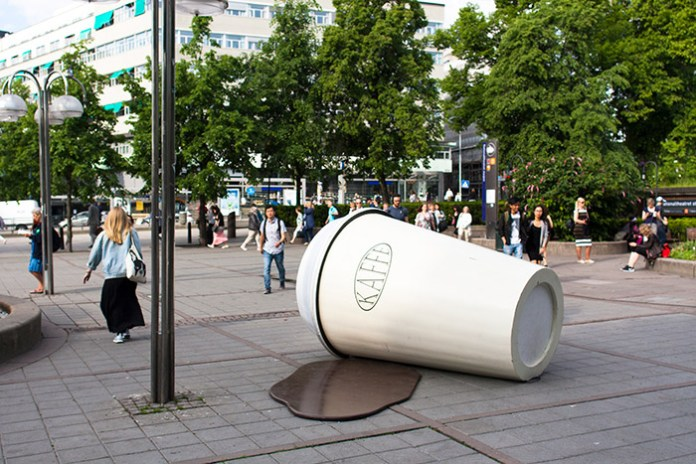 A sculpture of a spilled to-go coffee cup, in front of Nathionaltheateret in Oslo.