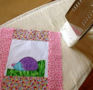 Ironing the samplers before finishing stitches