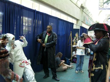 A photo of some cosplayers taking pictures of cosplayers (meta much?)