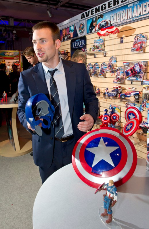 """Captain America"" movie lead Chris Evans examines the new Captain America toy line at Hasbro's Toy Fair showroom in New York"
