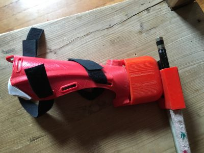 3D printed prosthetic bow holder with bow and velcro for attaching to the arm.