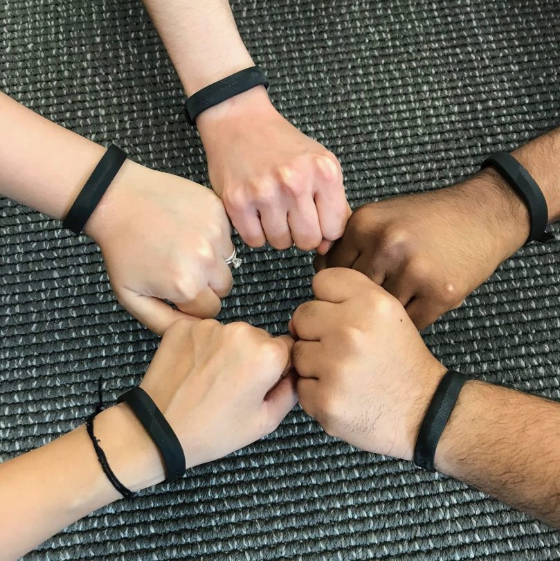 Hands in a circle wearing fitbits.