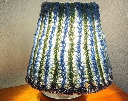 A picture of a knit lampshade in blue and green surrounding a lit lamp on an orange table.
