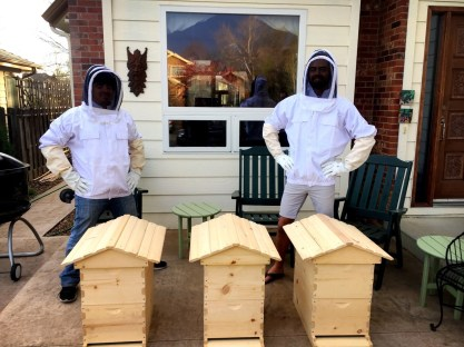 Sam and Montana proudly posing next to the bee boxes they built.