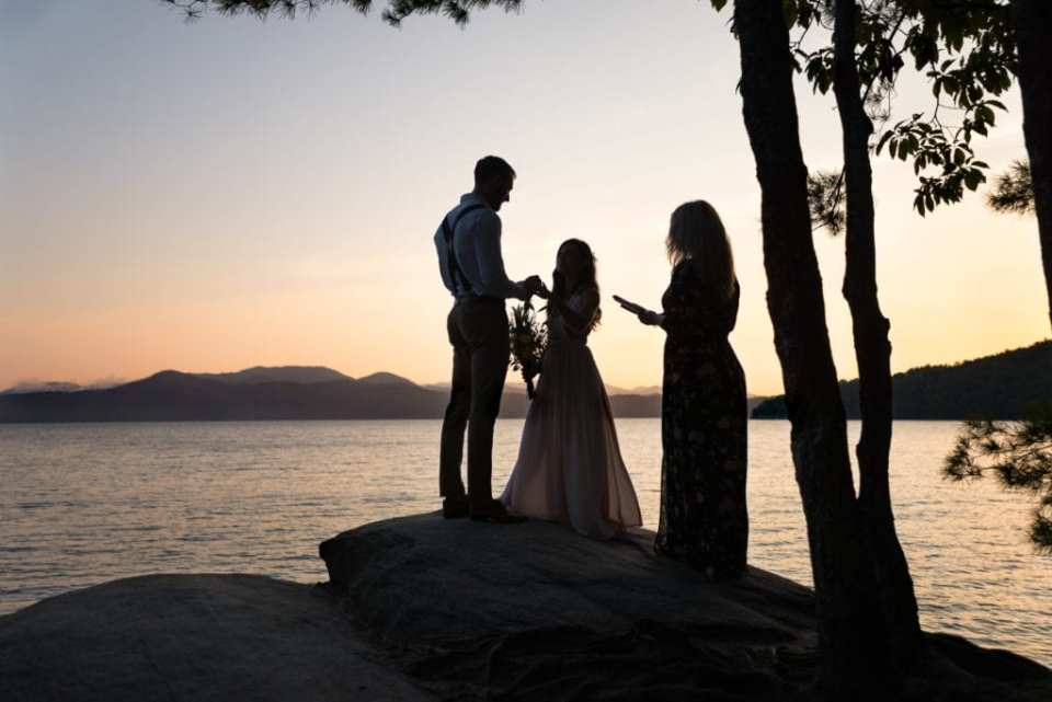 A bride and groom exchange rings in an adventure elopement ceremony on the top of a rock overlook overlooking a South Carolina lake at sunrise