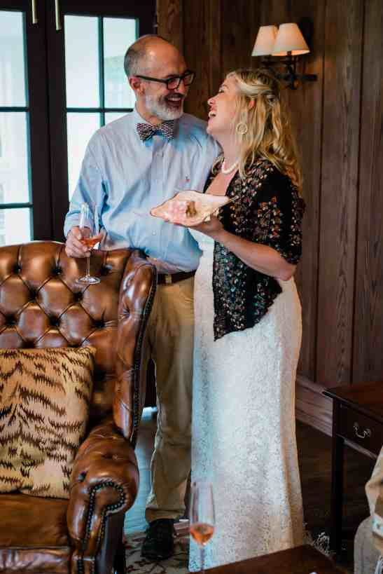 A bride and groom laugh, leaning together at an intimate wedding reception at Grey Stone Inn Library with an antique leather chair, rich wooden paneled walls and glass French doors visible behind them.