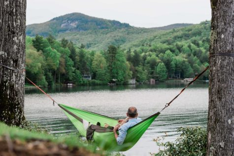 A bride and groom relax in a hammock after their elopement in the mountains near Brevard North Carolina. The hammock loverlooks a lake, a mountain summit and lush green trees. The groom holds a glass of champagne in his hand as they celebrate their elopement day.