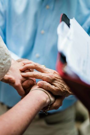 in an intimate adventure elopement with family, the image is a close up of the mother's hand covers the bride and grooms hands while she performs the ceremony as their officiant.