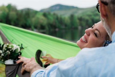 After their waterfall elopement in the Southeast, a bride and groom relax in a hammock together overlooking a beautiful lake, ringed with lush green mountains with trees. The bride leans back into the groom in the hammock in her wedding dress, smiling brightly, while he kisses her head as they relax after their elopement ceremony