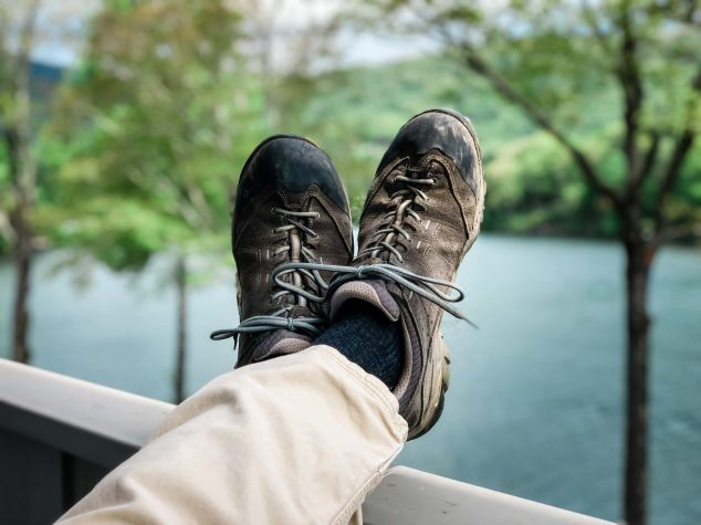 The wedding attire for the groom in an adventure elopement included his favorite scuffed and worn hiking shoes. Kicked up on the railing of the cabin , overlooking the lake while he waits for his partner to prepare for the ceremony.