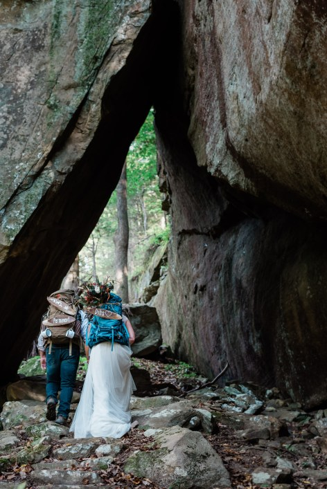 Hiking elopement with the bride and group walking under a natural stone arch in Kentucky with MAKE Adventure Stories Photography