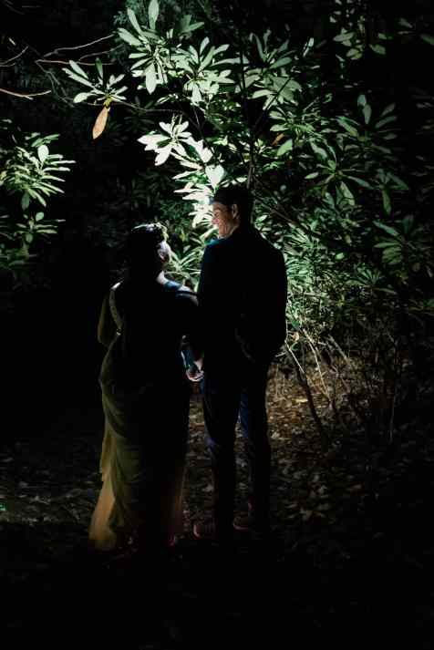 A bride an groom are hiking in the dark through low hanging rhodendron shrubs in an arc overhead
