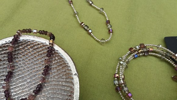 A handmade coil bangle bracelet, beaded bracelet and necklace from Green Feather Creations made with silver and gem beads.