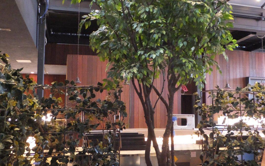 Custom Faux Ficus Trees, UV Boxwood Hedges, and Trellis Greenery.