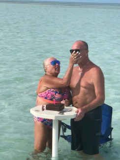 Newly married guests sharing cake at the sandbar