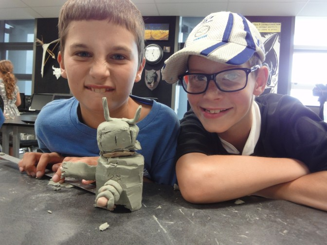 Students proudly pose with their clay robot