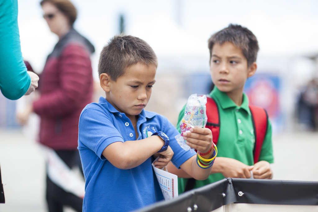 SAN MATEO, CA May 20 2016 - A young boy prepares to put on safety glasses at the 11th Annual Maker Faire Bay Area at the San Mateo County Event Center.