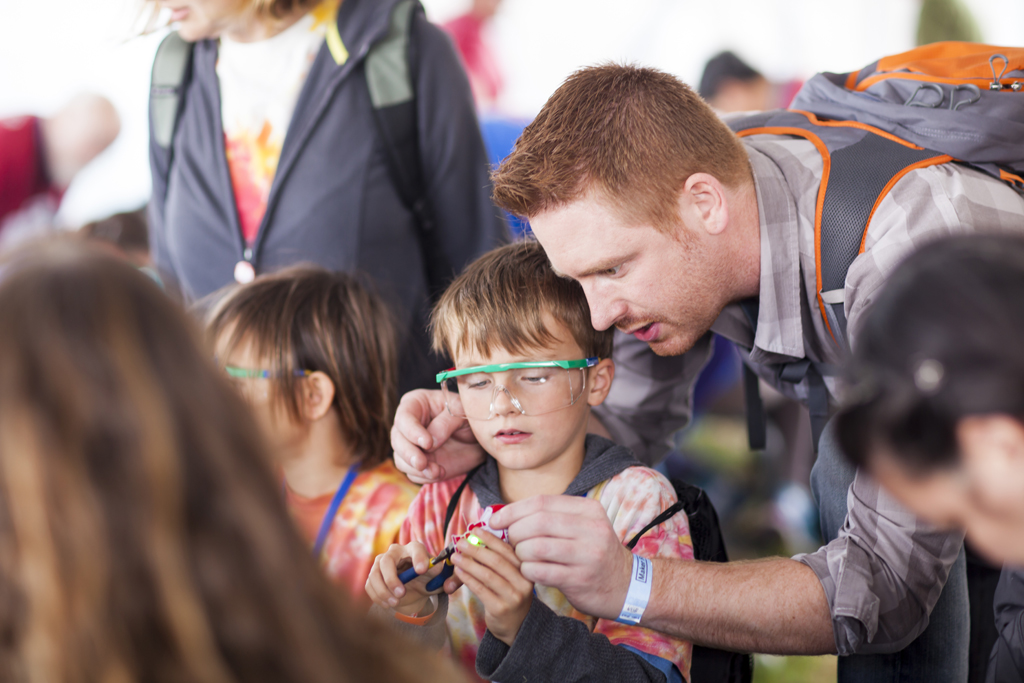 SAN MATEO, CA May 20 2016 - A father and son working togther at the 'Learn to Solder' activity station presented by Google at the 11th Annual Maker Faire Bay Area at the San Mateo County Event Center.