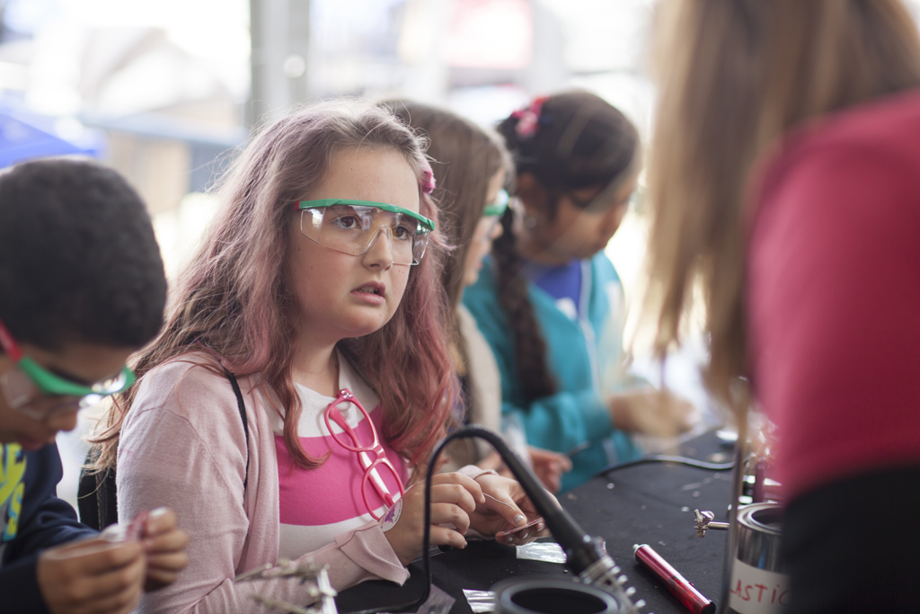 SAN MATEO, CA May 20 2016 - A group of girls working with electronics at the 'Learn to Solder' activity station presented by Google at the 11th Annual Maker Faire Bay Area at the San Mateo County Event Center.