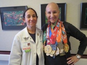"With Dr. Nerenstone, my medical oncologist, showing off all my medals earned while undergoing breast cancer treatment up until my final chemo ""therapy"" (Aug-Jan). That's 3 full marathons (including 2 world majors), 5 half marathons, 1 10-miler, 3 10-k's, 5 5-k's, plus a Dumbo, Goofy, Dopey and a Coast to Coast! (Total medal count - 21)"
