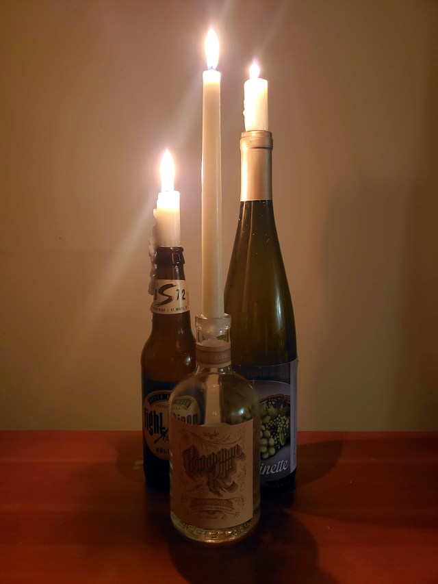 candlesticks burning in alcohol bottles