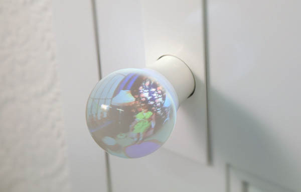 Glass lens doorknob gives preview of room beyond