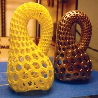 """3D printed yellow plastic draft of the """"Klein Bottle Opener"""" next to a finished model printed in brass and bronze from Shapeways."""