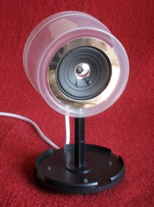 The speakers are mounted on a stand made from a repurposed CD spool case.