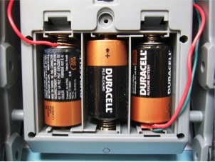 A close up of the battery compartment. Note the two wires with a thin insulator between them at the lower right. The red wire steals the power from the batteries, send it to the outboard switch, which either sends it right back via the green wire, or sends it to the external bulb.