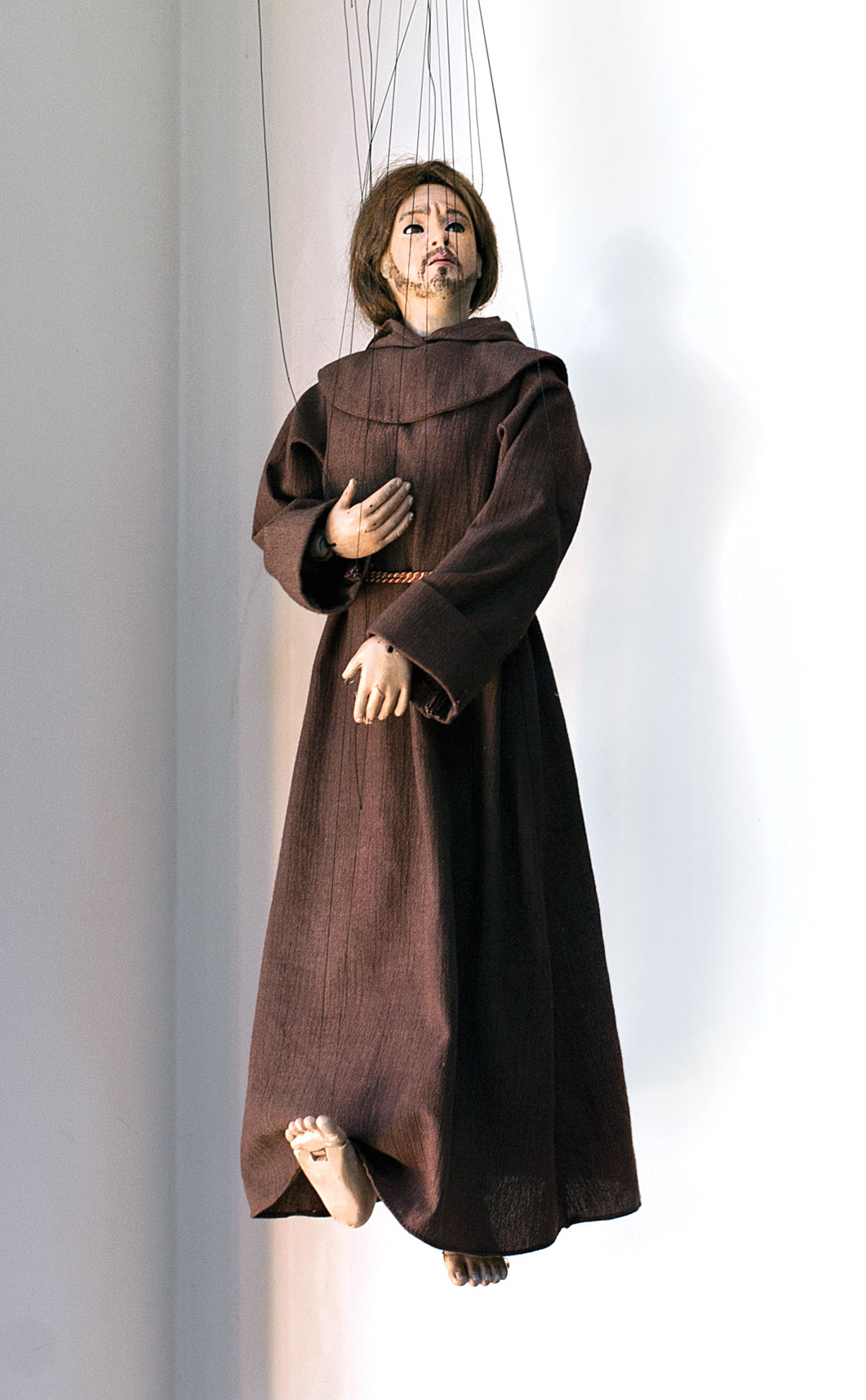 a complex marionette with detailed face and hands dressed in a brown monk's robe