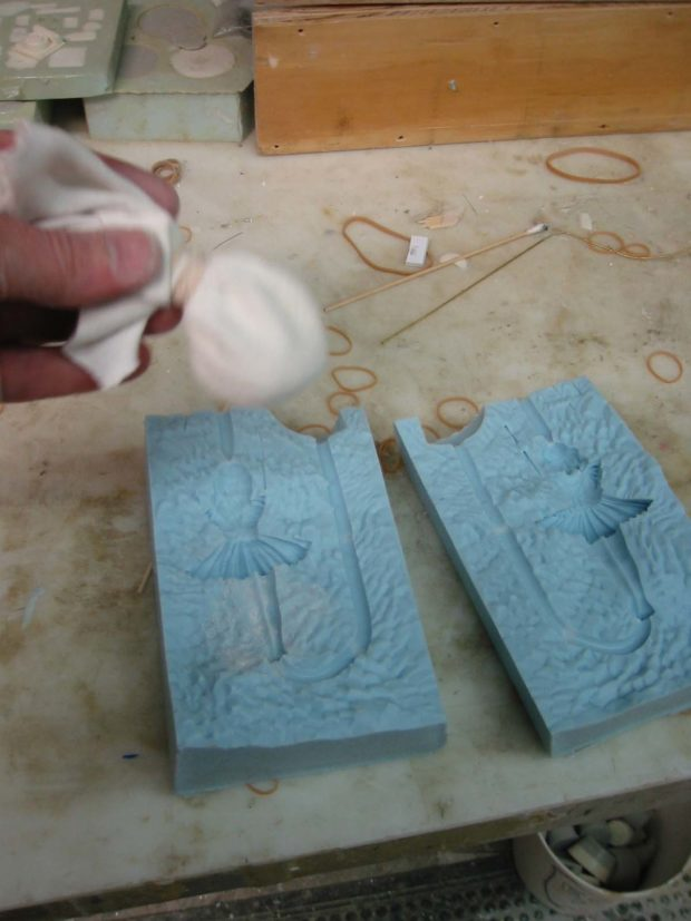 Fig. P: Dusting the mold with release agent (cornstarch or talcum powder).